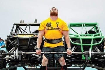 Muscle up! Strong men hit the beach